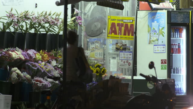 Cars and people go by an outdoor florist / convenience store at night
