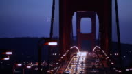 Cars cross the silhouetted Golden Gate Bridge at night.