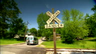 MS Cars crossing over railroad crossing in both directions frame 'Railroad Crossing' Xsign 'Danger' sign on post frame rural town houses along street...
