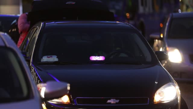 Cars displaying Lyft Inc window stickers picking up a riders at Los Angeles International Airport in Los Angeles California US on Monday November 13...