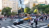 T/L Cars driving by busy city street intersection with pedestrian crossing the street / New York City, New York, United States