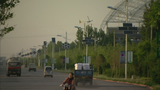 WS Cars driving down street lined with solar panels, Dezhou, Shandong, China