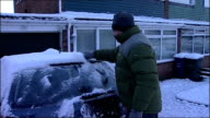 Cars driving in snow / Good scenes of snowy countryside ENGLAND Tyne and Wear Sunderland Man scraping snow from the windscreen of his car SOT INT CAR...