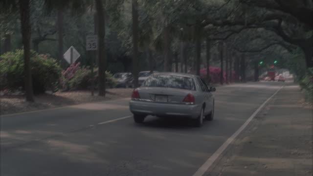 TU Cars driving on tree-lined residential street / Savannah, Georgia, United States