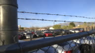 Cars in impound lot behind barbed wire fence