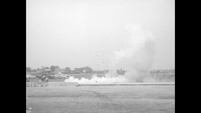 WS cars on trailer car in center of frame on dirt field at fairground cloth 'coffin' in front begins to emit smoke explodes / stunt man in helmet who...