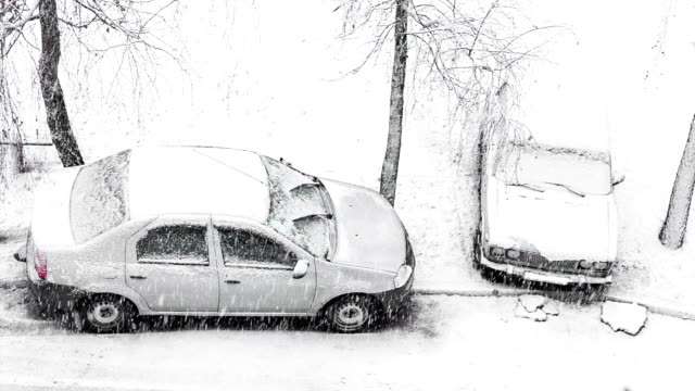 Cars parked on the roadside in winter time.
