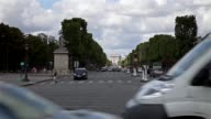 Cars passing by in front with perspective of Champs Elysées of Paris in the background