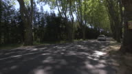 MS Cars running through rural road sheltered by trees / France