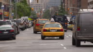 cars travel down 7th ave during the daytime.  Taxi cabs line up and turn left.
