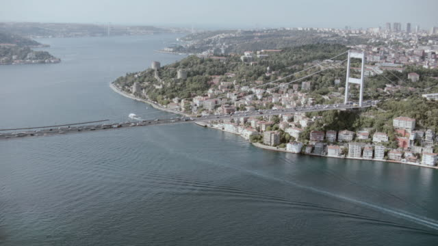 AERIAL Cars traveling on bridge across expansive waterway with high end villas on the shoreline /
