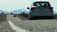 WS Cars traveling on road, trees and snowcapped mountains in background / Mackenzie District, Canterbury, New Zealand