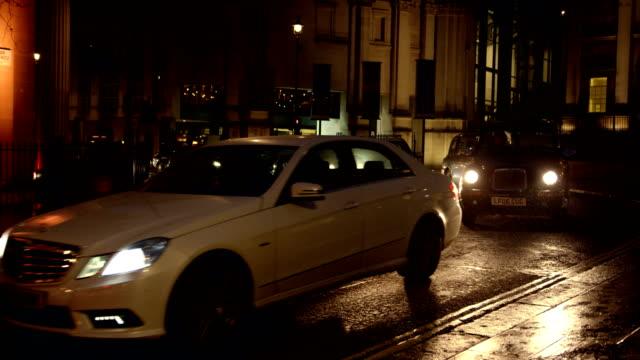 Cars turning to Trafalgar square in London in slow motion at night on rain.