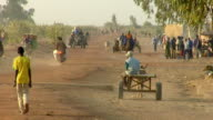 WS, Carts and people on busy dirt road, near Niono, Mali
