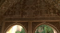 MS, TD, Carved arches and garden with fountain behind window in Alhambra palace, Granada, Andalusia, Spain