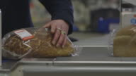 A cashier at a UK supermarket individually scans loaves of white and brown bread.