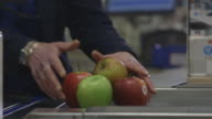 A cashier at a UK supermarket scans apples from a conveyor belt.