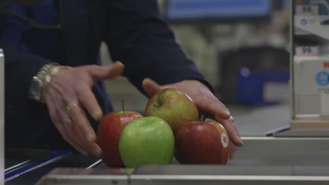 A cashier at a UK supermarket scans apples from a conveyor belt.
