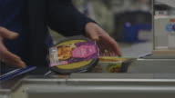 A cashier passes a range of ready meals through a till as they arrive on a conveyor belt at a UK supermarket.