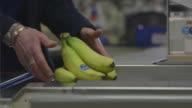 A cashier passes various popular fruits through a till at a UK supermarket.