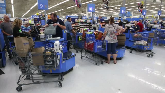 A cashier scans school supplies for a customer at a WalMart Stores Inc location in the Porter Ranch neighborhood of Los Angeles California US on...