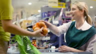 Cashier talking to customer at supermarket checkout