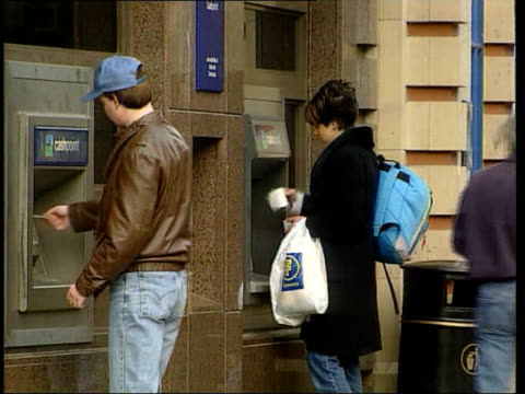 Stephen Byers meeting LIB ENGLAND London EXT Woman as withdraws money from Lloyds TSB cashpoint Man woman standing at separate cash machines as...
