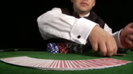 Casino dealer fanning deck of cards across table, flipping cards face up and down, and unspreading deck