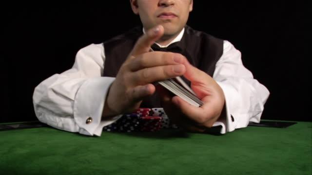 Casino dealer shuffling cards on table