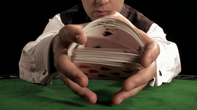 Casino dealer shuffling deck of cards in front of camera on table