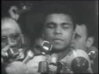 Cassius Clay outside courthouse in the midst of reporters and microphones / picketers outside courthouse holding signs / reporters and microphones...