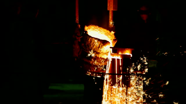 Casters at foundry Рouring melted metal into a form closeup
