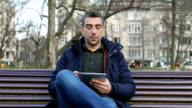 Casual male with digital tablet looking at camera