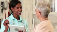 CU PAN Casually Dressed Doctor Reviewing Digital Patient Records with Senior Woman / Richmond, Virginia, United States