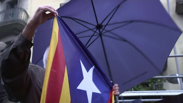 Catalonia refuses to back down over independence Catalonia Barcelona EXT High angle view of crowd of protesters Protester holding umbrella Various...