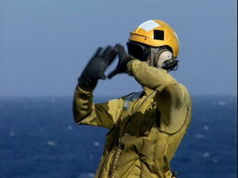 A catapult officer directs activities on deck by hand signals as pilot of F 18 awaits take off USS Eisenhower 1998