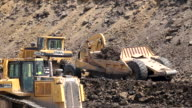 Caterpillar construction vehicles excavate a building site that will house new commercial and residential units 1080p HD