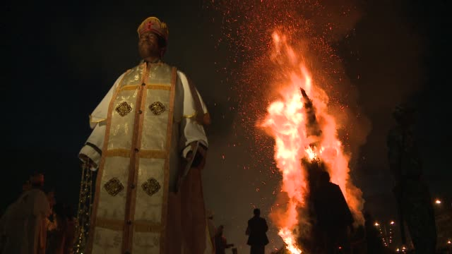 A Catholic priest stands before a burning effigy during a religious ceremony. Available in HD.