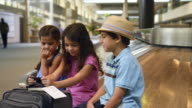 Caucasian brother and sisters waiting at airport using cell phone