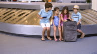 Caucasian brother and sisters waiting at airport using cell phones