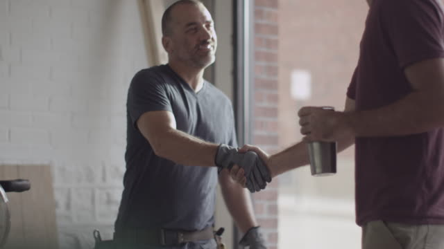 Caucasian construction workers shaking hands