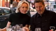 Caucasian couple reading menu in restaurant