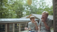 Caucasian father and son eating donuts at lake home
