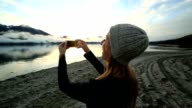 Caucasian female by the lake captures landscape on mobile phone
