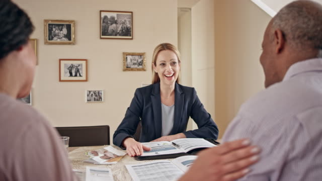 Caucasian female insurance agent advising a senior couple in their home