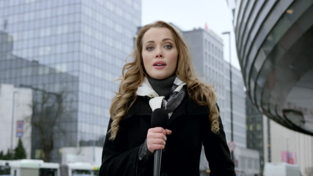 Caucasian female news reporter reporting from the business district