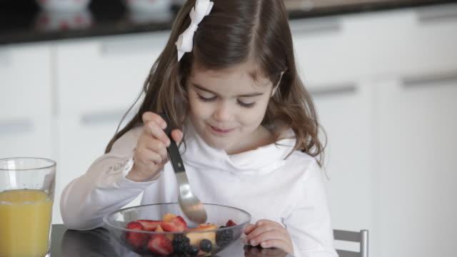 Caucasian girl eating fruit salad