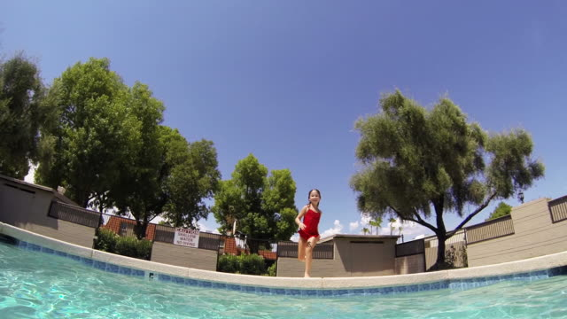 Caucasian Girl Jumping Into Swimming Pool Stock Footage