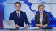 LD Caucasian male and female anchor presenting the news
