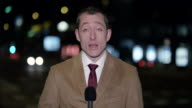 Caucasian male correspondent reporting from the city at night